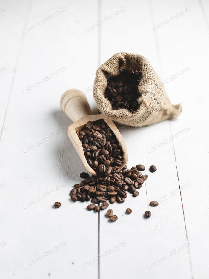 coffee beans in wooden scoop and bag with white wood background