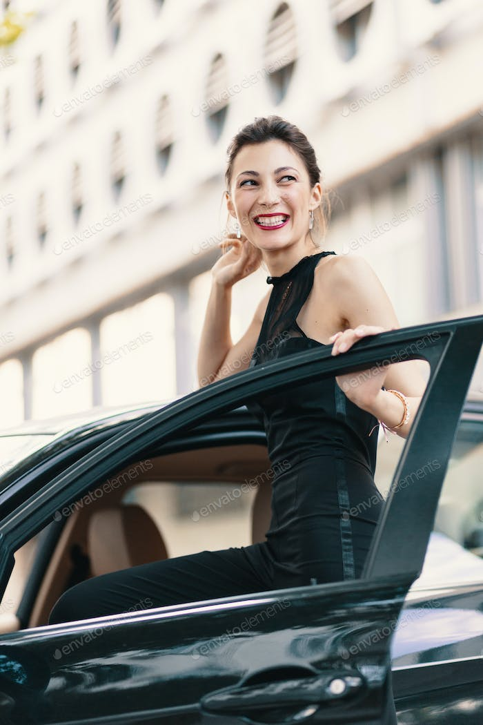 Lovely laughing woman standing with a happy look in the door of a car ready to win the world