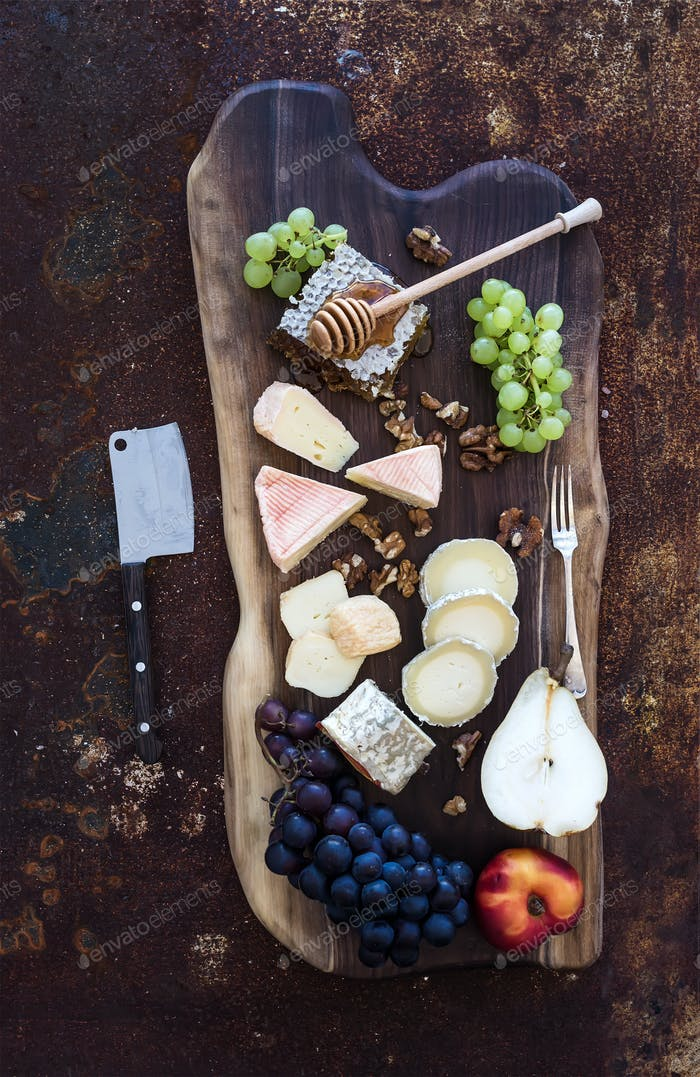 Wine appetizers set: French cheese selection, honeycomb, grapes, peach and walnuts