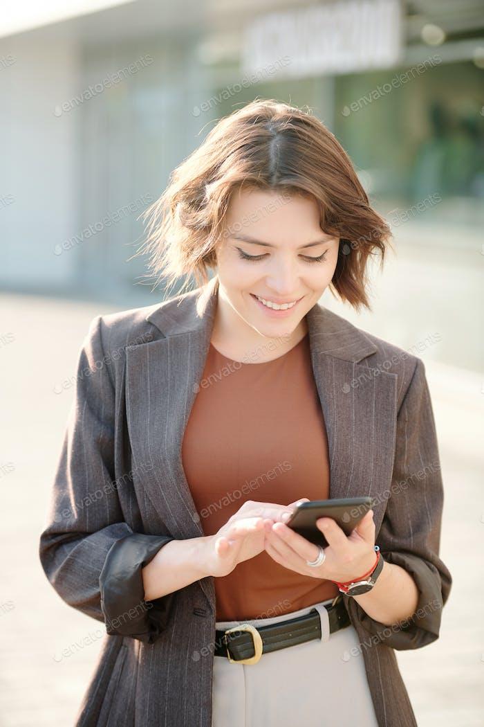 Счастливая и элегантная молодая бизнесвумен, прокручивающая контакты в смартфоне