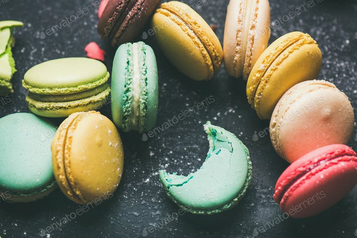 Sweet colorful French macaroon cookies over black background
