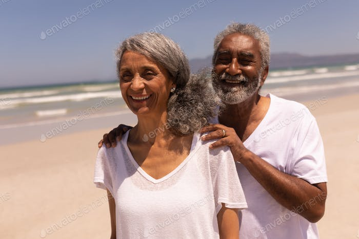 Front view of senior man standing with hands on senior woman shoulders at beach in the sunshine