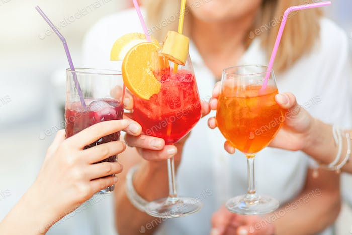 Cheers with different colored cocktails.
