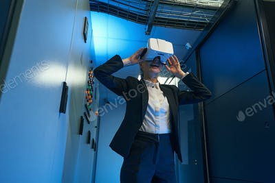 Young woman wearing virtual reality glasses indoors