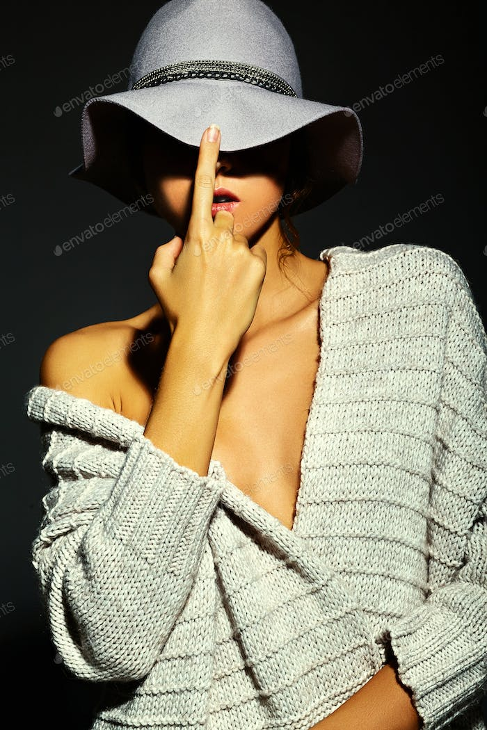 Woman in hat posing in studio