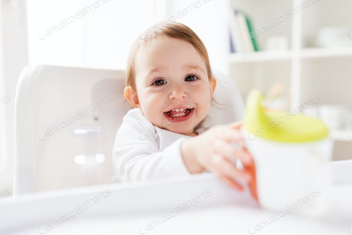 baby drinking from spout cup in highchair at home