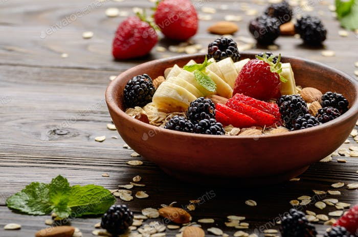 Fruit healthy muesli with banana strawberry almonds and blackberry in clay dish