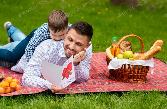 Best Father's Day greeting. Father and son with card cuddling on plaid in park during picnic