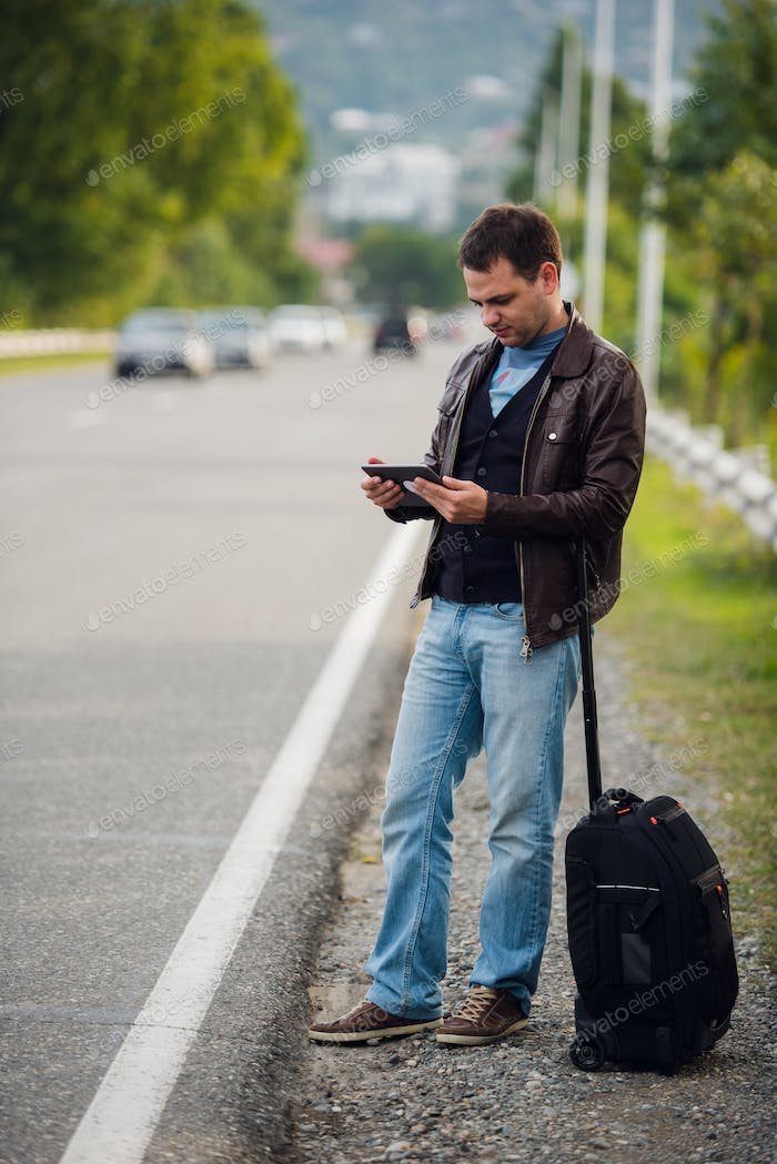 man standing with digital tablet waiting for car or taxi. Hitchhiking