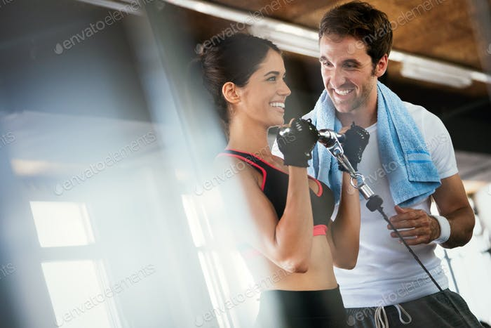 Portrait of pretty woman training in gym with her trainer helping