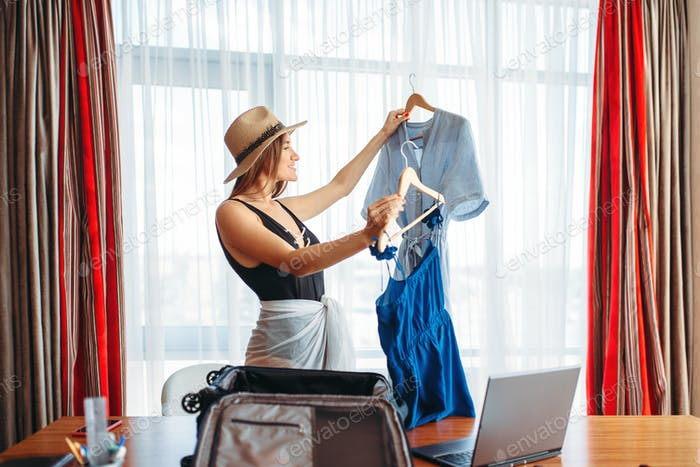 Woman selects outfits, thinking about voyage
