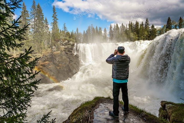 Turismo fotógrafo de Naturaleza con tomas de cámara mientras está de pie Ri