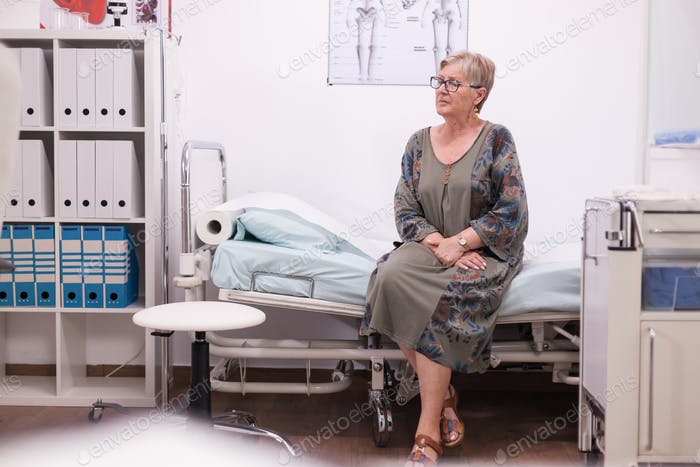 Elderly woman sitting on hospital bed