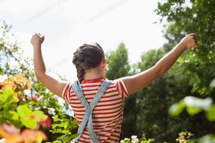 Rear view of girl standing with arms raised amidst plants against sky