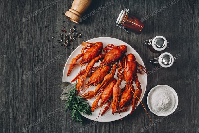Boiled big red fresh crawfish in white plate with green herbs