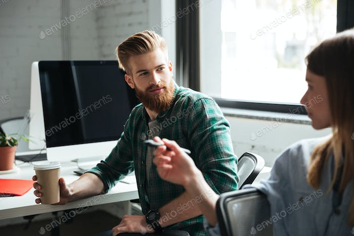 Two young concentrated colleagues work in office