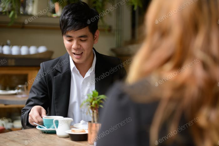 Happy young Asian business couple drinking coffee together at the coffee shop