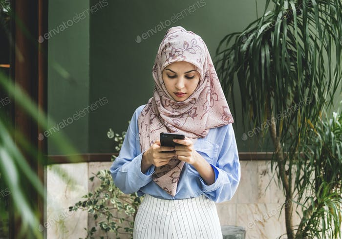 Islamic woman texting messaging on the phone