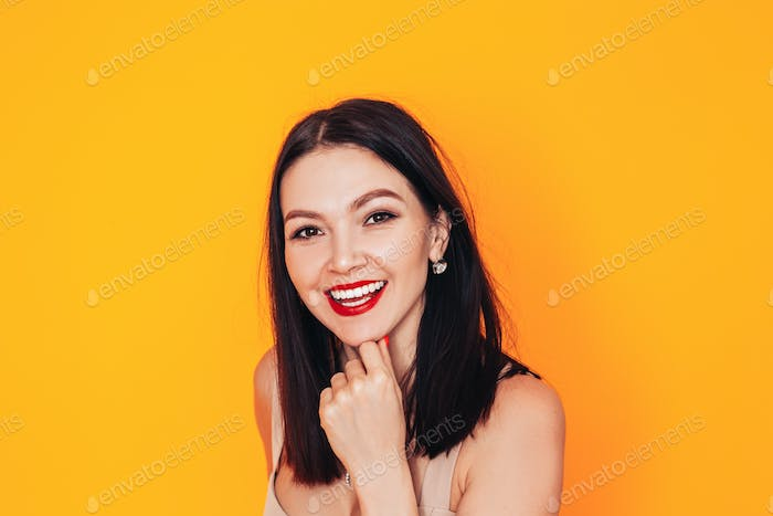 Young woman standing in front of a yellow background. Dental clinic advertisement