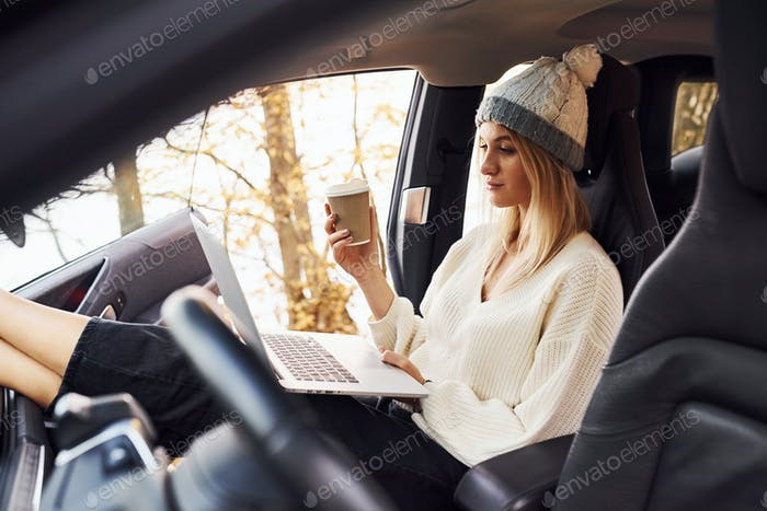 Girl have autumn trip by car. Modern brand new automobile in the forest