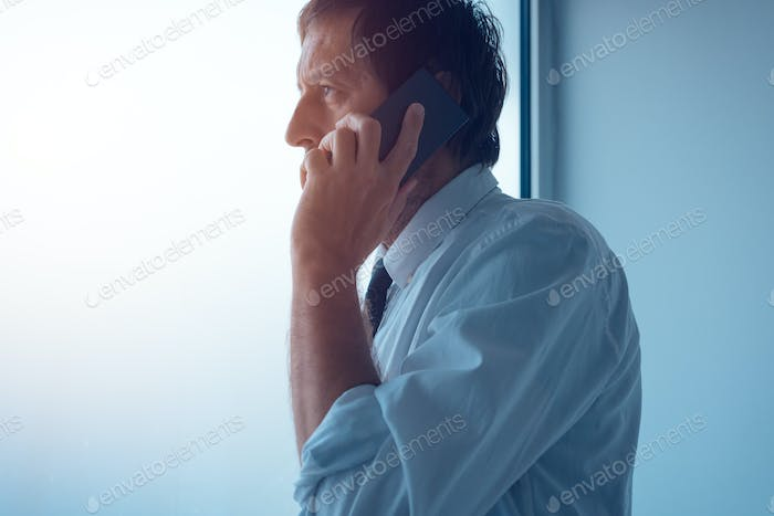 Businessman standing next to office window and talking on mobile