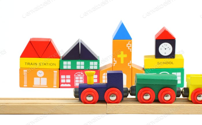 Wooden train on the railroad and houses made of toy blocks  isolated over white