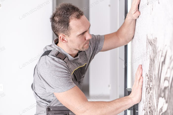 Caucasian Men Installing Wallpaper on His Bedroom's Wall
