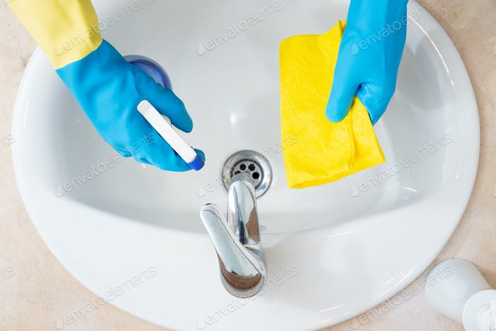 Hands with protection gloves cleaning a bathroom
