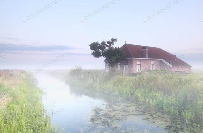 granja por río en niebla