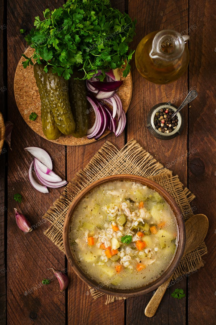 Soup with pickled cucumbers and pearl barley - rassolnik on a wooden background. Top view.