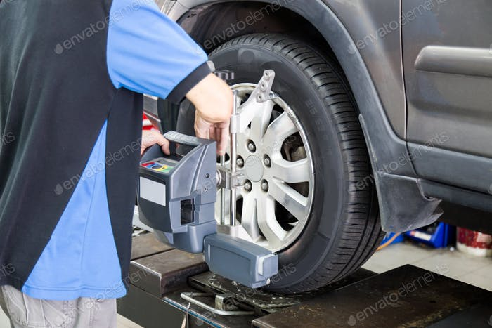 Mechanic fixing a wheel alignment devise onto the wheel of a vehicle in garage