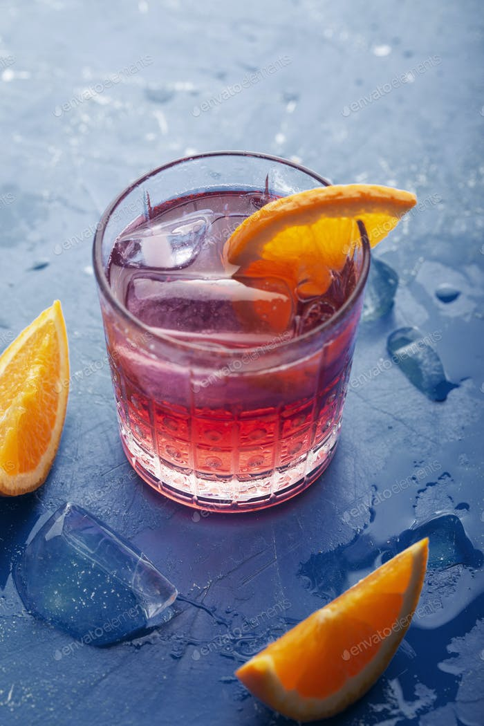 Fresh ice tea summer cocktail with orange and ice. Background toned in modern blue color 2020