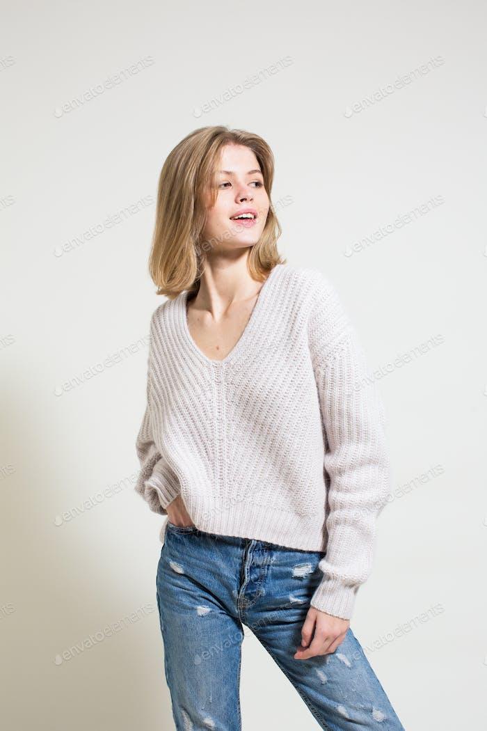 Studio fashion shoot. Charming model posing on white background.