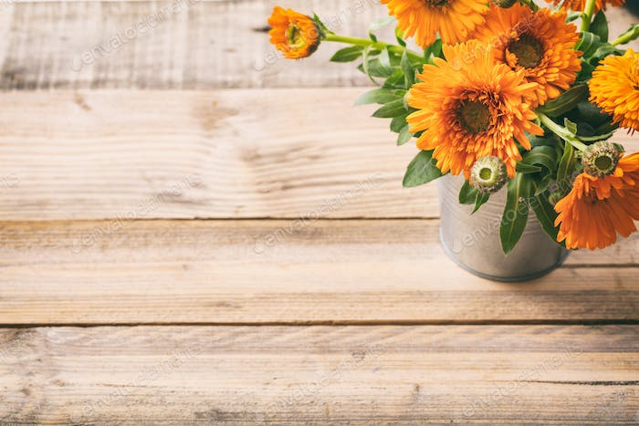Calendula on wooden table, copy space, view from above