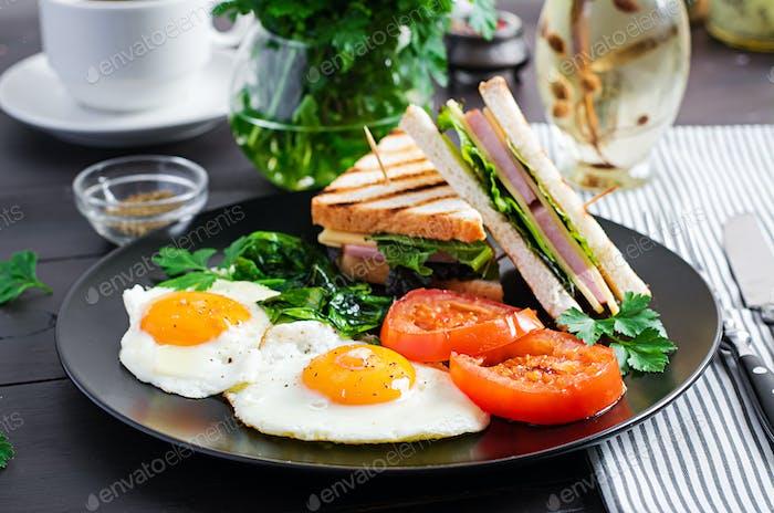 Frühstück: Spiegelei, Spinat, Tomaten und Club-Sandwich auf Teller.