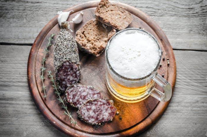 Scheiben von Französisch Saucisson Wurst mit Glas Bier