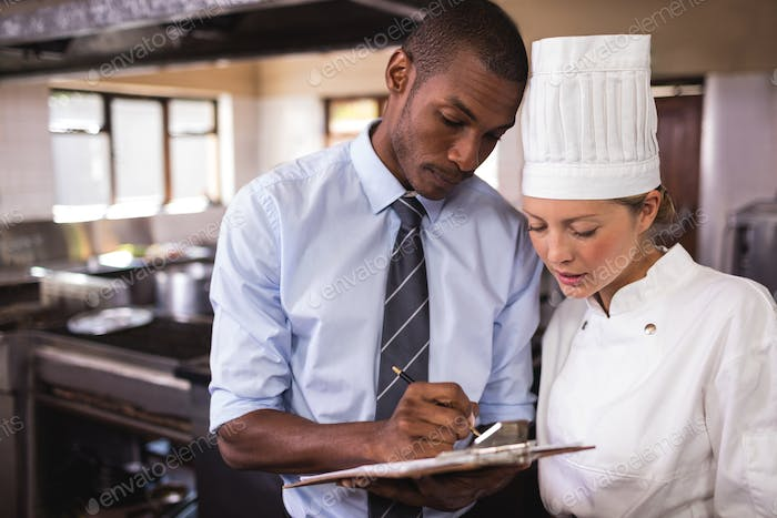 Male manager and female chef writing on clipboard in kitchen at hotel