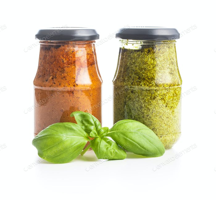 Green basil and red tomato pesto dip sauce in jar and basil leaves.
