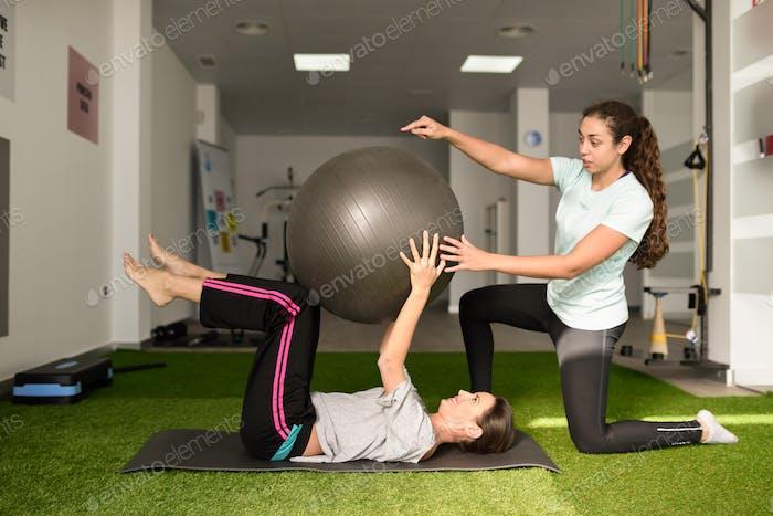 Physiotherapeut unterstützt junge kaukasische Frau mit Bewegung