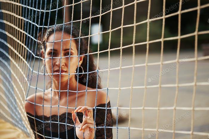 Ernsthafter Blick. Brunette steht tagsüber hinter dem Volleyballnetz