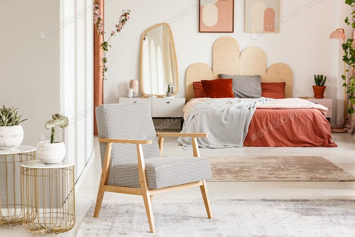 Patterned wooden armchair next to gold table in orange bedroom i