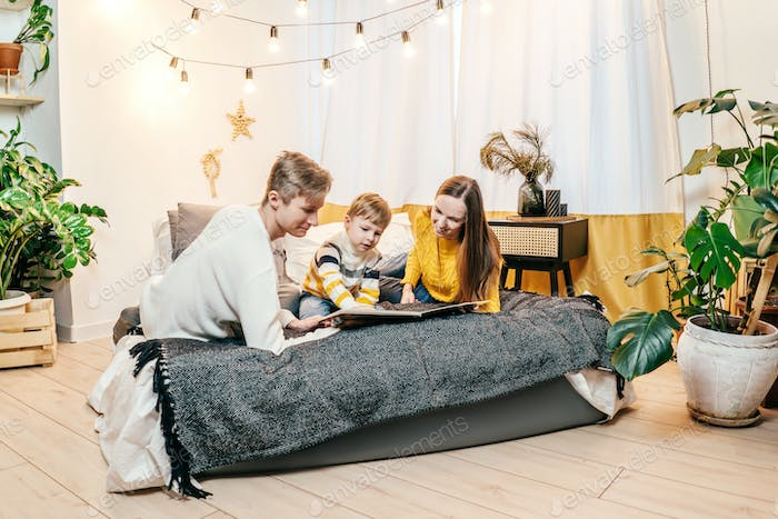 Happy family with book, yellow gray colors.