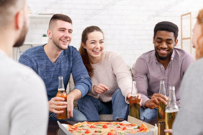 Excited friends talking and eating pizza at home