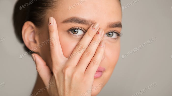 Young woman looking at camera through fingers