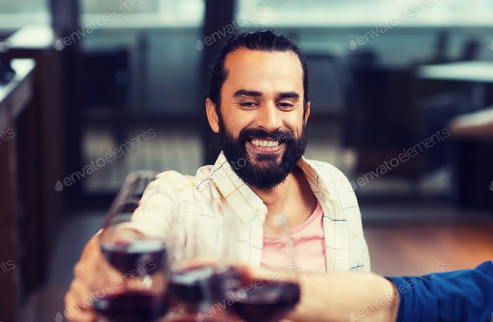 happy man clinking glass of wine at restaurant