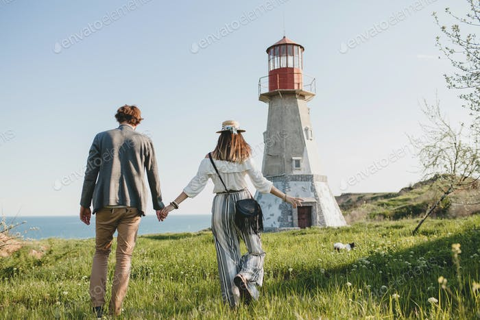 romantic young hipster couple indie style in love walking in countryside