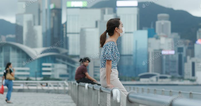 Woman wear face mask and look at the city in Hong Kong