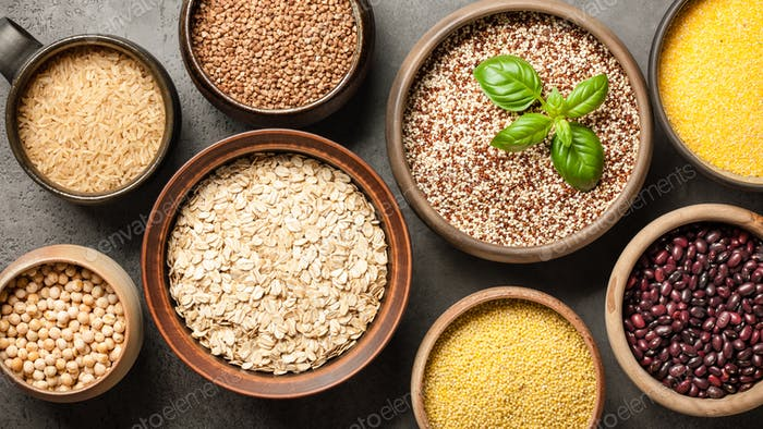 Set with various cereal grains and legumes on stone background