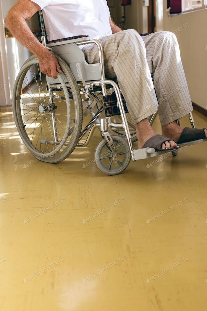 Low section of senior Caucasian male patient sitting in wheelchair in corridor at retirement home