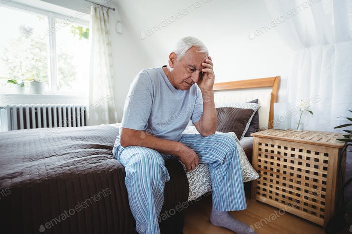 Frustrated senior man sitting on bed